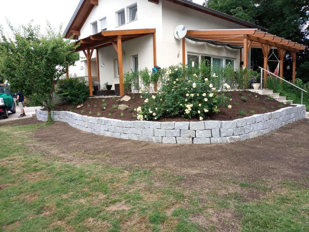 Terrasse mit Beet an Steinmauer